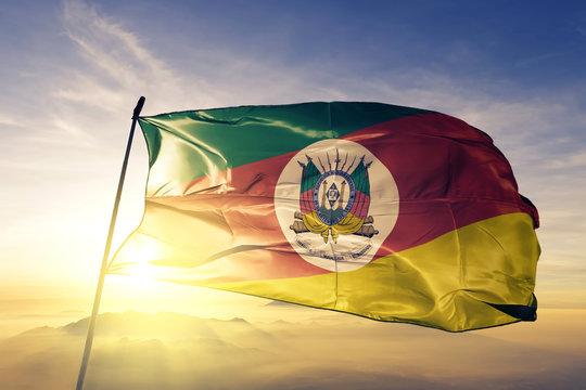 Rio Grande do Sul state of Brazil flag waving on the top sunrise mist fog