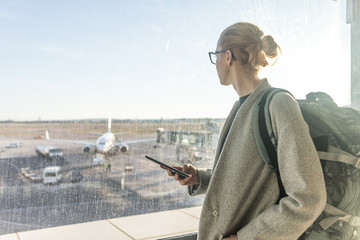 Casually dressed female traveler at airport, holding smart phone device, looking through the airport gate windows at planes on airport runway.