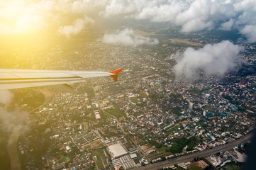 Landscape images of The wings of the plane Which is flying in the sky Above the city with desnse buildings, to travel and transportation concept.