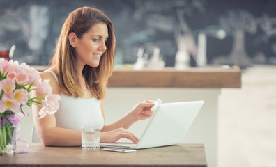 Attractive young woman online shopping using computer and credit card in home kitchen