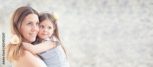 Happy mother's day concept. Portrait of loving mother with her daughter on her hands. Panoramic banner with copy space.