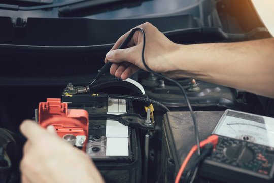Close up car mechanic is using the car battery meter to measure various values and analyze it.