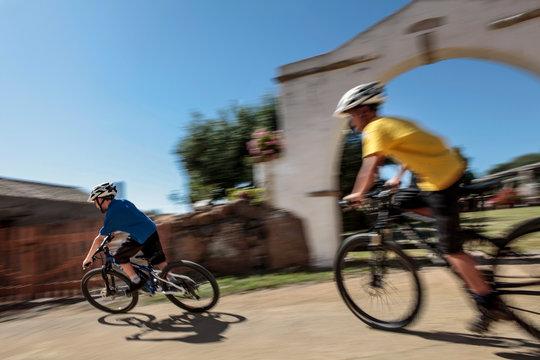 Ciclisti che pedalano in un borgo - Sardegna