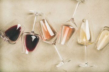 Foto op Aluminium Wijn Flat-lay of red, rose and white wine in glasses over grey concrete background, top view. Wine bar, winery, wine degustation concept