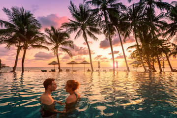 Couple at beach vacation holidays resort relaxing in swimming pool with scenic tropical landscape at sunset, romantic summer honeymoon island destination, coconut palm tree near the sea