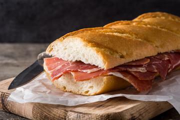 Photo sur Aluminium Snack Spanish serrano ham sandwich on wooden table.