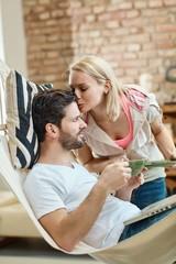 Woman kissing boyfriend at home