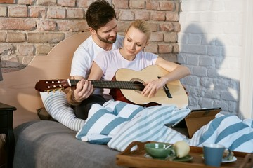 Romantic couple playing the guitar together