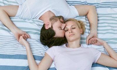 Loving couple lying on bed heads together