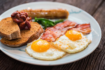 Typial breakfast with eggs, bacon and sausage on plate