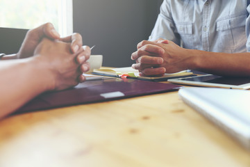 The hands of two men on a wooden table.Negotiation concept Or job interview