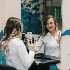 young woman takes a selfie in a beauty salon .