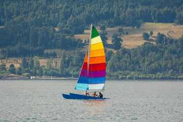 Colorful sailboat with rainbow color stripes, with a group of locals or tourists enjoying, with mountains and forests on the background. Sailing in Villarrica lake in a warm summer sunny day