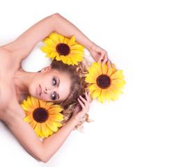beautiful woman model lying among the flowers of a sunflower.