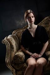 Elegant young woman sitting on sofa