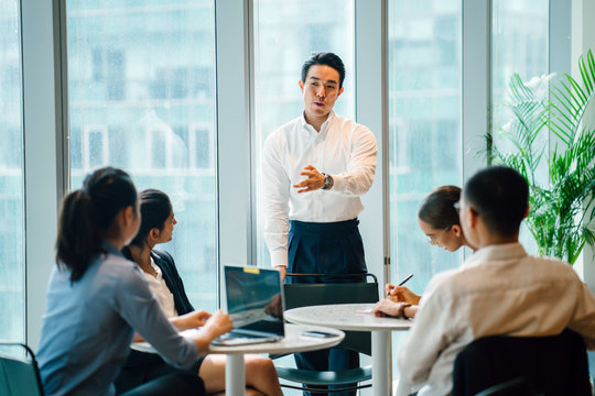 A gorgeous, sure, and fit Asian Chinese man seats a gathering with his group amid the day in the workplace. He is expertly wearing a shirt and pants and is motioning as he talks.