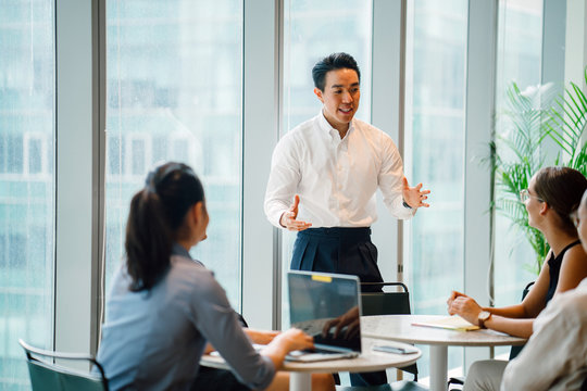 A good looking and confident Asian Chinese man is presenting in a meeting with his team during the day in the office. He is professionally dressed in a polo and pants and is gesturing as he speaks.