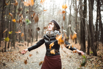 Woman throwing dry leaves in the air