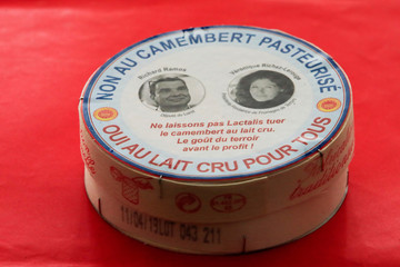 A box of a non-pasteurized French Camembert cheese with the pictures of French deputy Richard Ramos and Veronique Richez-Lerouge, president of Fromages de Terroirs, is seen at the National Assembly in Paris