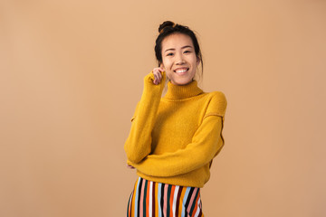 Image of gorgeous japanese woman wearing sweater smiling and looking at camera