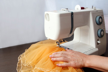 sewing machine working part with yellow cloth and seamstress hands