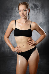 Sporty slim woman with fit and athletic body after training and workout