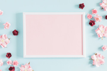 Flowers composition creative. Blank photo frame, pink flowers on pastel blue background. Flat lay, top view, copy space