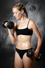 Muscular, fit and sporty woman exercising with dumbbells and weights in the studio