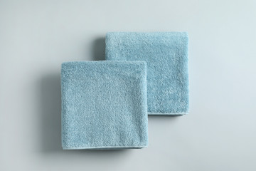 Fresh fluffy folded towels on grey background, top view. Mockup for design