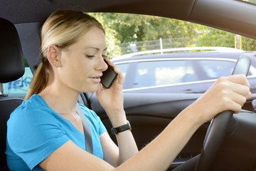 Woman as a driver is unfocused and on the phone during the car ride