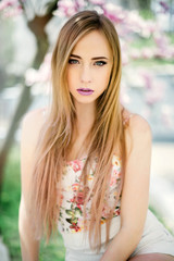 Close up portrait of young attarctive blonde girl posing near beautiful Magnolia flower tree on blooming season. Spring time