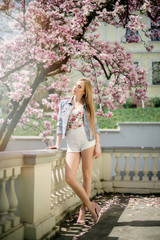 Young blonde woman in bright clothes posing near the blooming magnolia flower tree outdoors. Spring blooming season