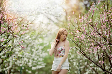 Portrait of young sensual blonde girl posing near beautiful Magnolia flower tree on blooming season. Spring time.
