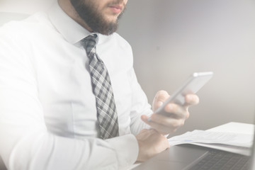 Young bearded businessman. Businessman work with computer on table in office work. Financial business. Light background. Close up. Office work with a laptop. Smartphone in hand.