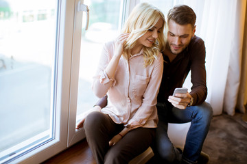 Loving couple use wireless internet at apartment, sitting near window, enjoy day light and using mobile phone