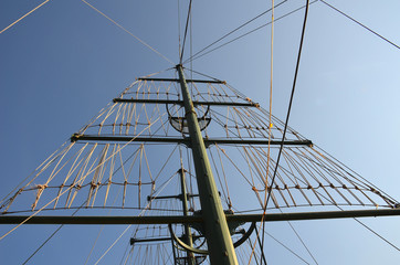 Mast on a yacht with a lot of ropes against a sunny blue sky on a summer day