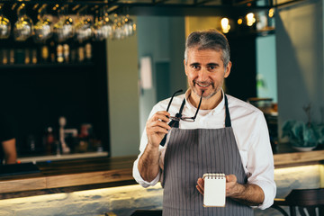 middle aged barman standing beside counter in cafe bar