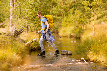 Young man crosses a mountain stream during a hiking on a sunny day