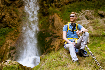 Handsome young red hair hiker stopped beside a mountain waterfall to rest