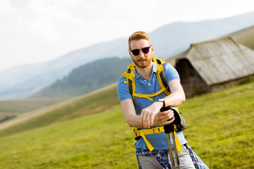 Handsome young red hair man with sunglasses hiking on the mountain