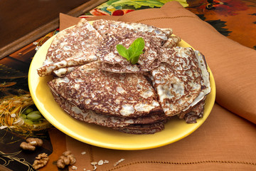 Pancakes on a yellow dish with brown napkin