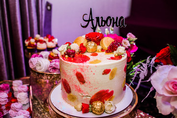 "Beautiful cake decorated of candies and roses with the inscription ""Alena"""