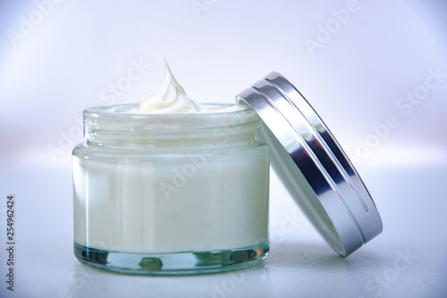 open glass jar of cream with a shiny lid on the glass table