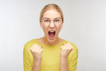 Portrait of a European girl in spectacles celebrates success and victory, clenches fists and shouts loudly from happiness, emotions of joy on the face of a young blonde woman in the white studio