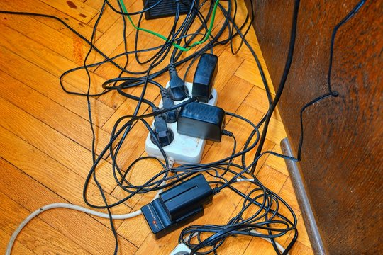 Tangled wires and battery charges on parquete floor. Domestic appliances.  Wires mess in domestic room