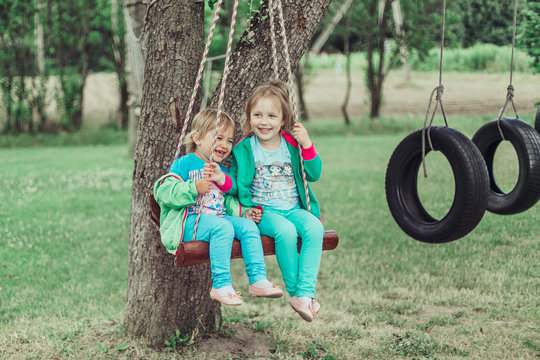 Two cheerful adorable girls riding on a swing together, smiling anh have fun in green summer park