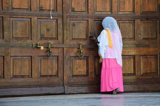 Betende Frau an einer Holztüre