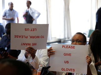 Senior doctors at Parirenyatwa General Hospital, Zimbabwe's biggest medical centre, hold placards during a  demonstration to protest a lack of medicines, gloves and bandages in Harare