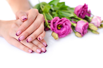 Acrylic Prints Manicure Hands of a woman with pink french manicure and flowers eustoma on a white background