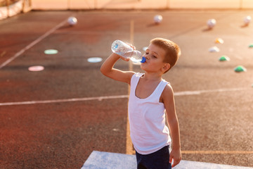 Boy drinking water from bottle and standing on the court after exercising.